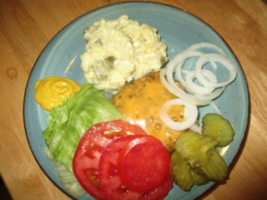 Plate full of burgers and potato salad.