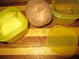 potato sliced in yellow container for traditional Irish colcannon