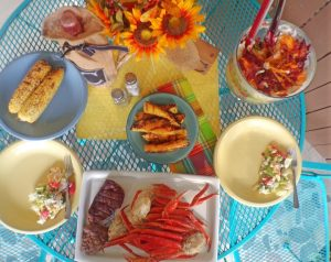 Table of grilled food and 7 layer salad