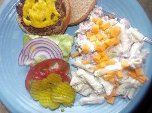 Chicken bacon ranch pasta salad with a hamburger plated.